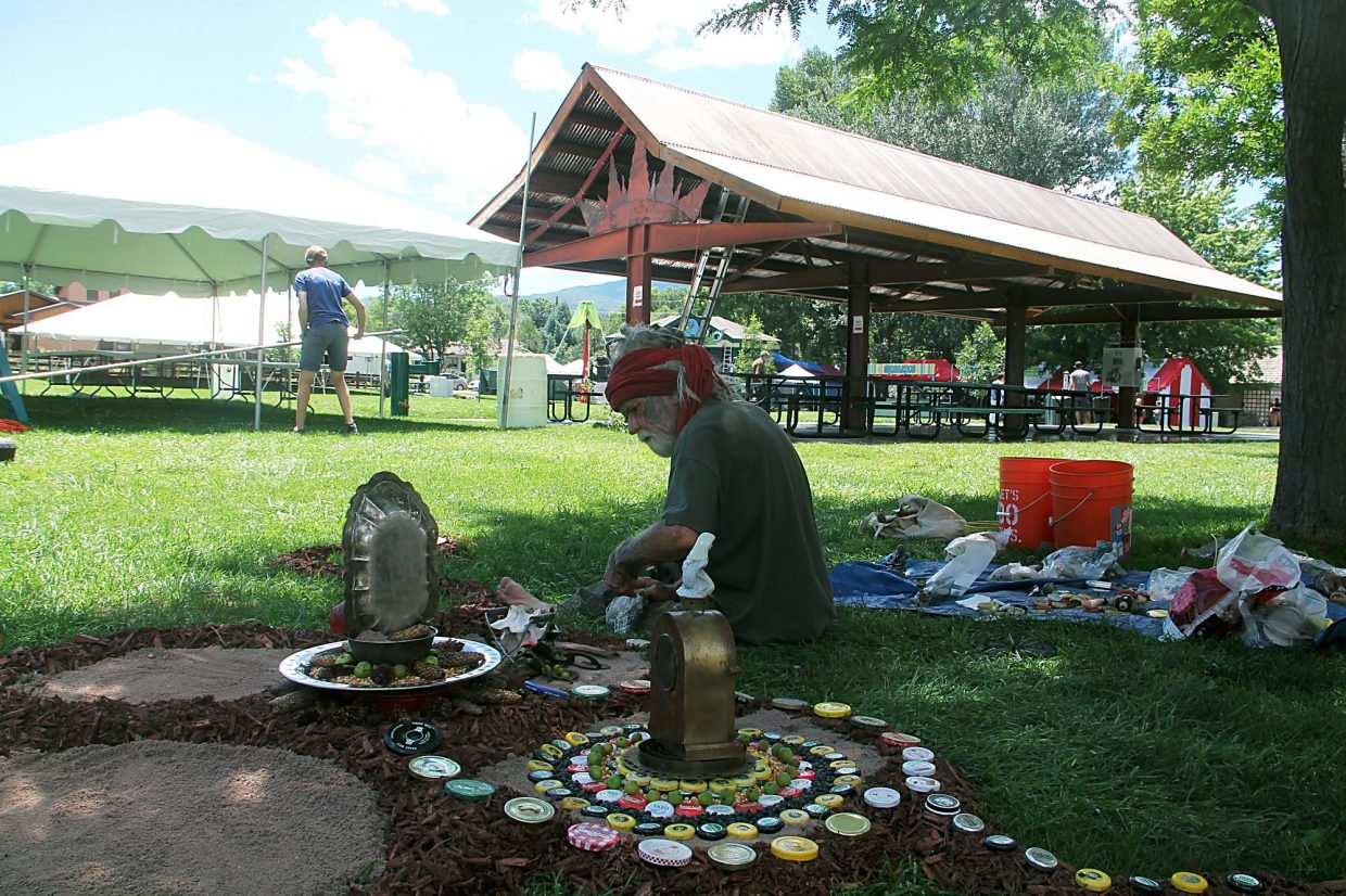 Robert Moondragon constructs a mandala of his own as set-up begins for the 44th Carbondale Mountain Fair.