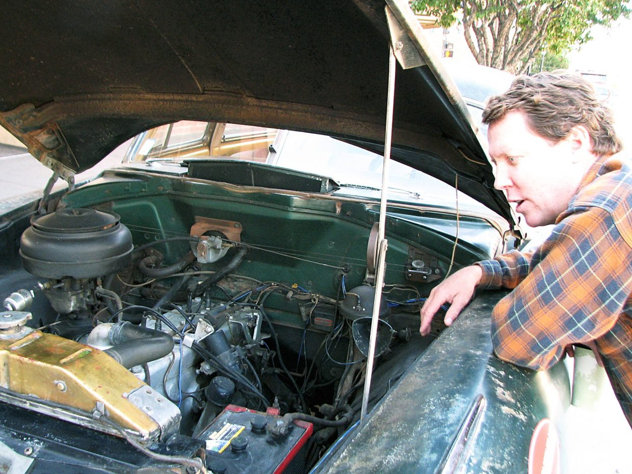 Dan McNichol looks under the hood of his 1949 Hudson, which he is driving across America to study and draw attention to infrastructure issues. McNichol, from Boston, writes about a range of infrastructure issues, including the Big Dig tunnel in Boston.