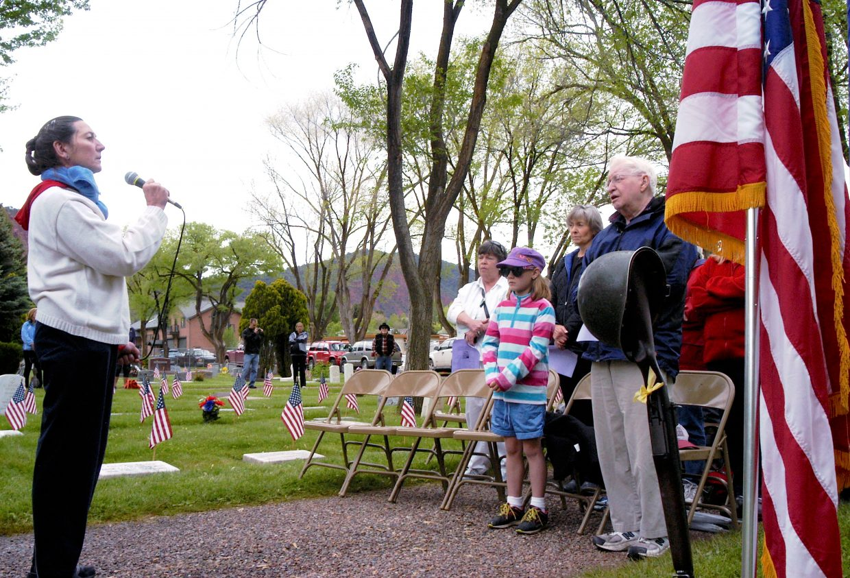 Amanda Madden, 8, of Glenwood Springs, is joined in the front row by her grandfather and Korean War veteran Neil Kilcoyne, who was visiting from New Jersey, as Catherine Zimney sings America the Beautiful during the traditional Memorial Day commemoration at Rosebud Cemetery in Glenwood Springs on Monday.