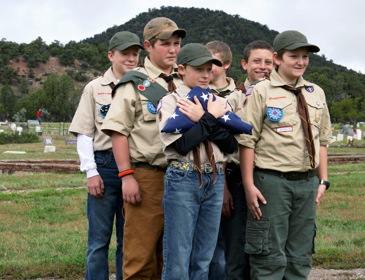 Members of Boy Scout Troop No. 221 prepare to deliver the flag during a ceremony at Highland Cemetery Monday.