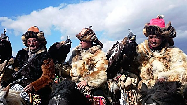 Great eagle hunters in Mongolia pose for a photo.
