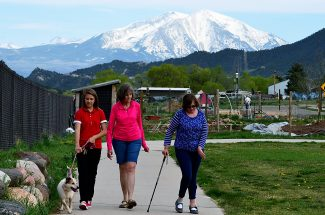 Alice Brouhard, center, walks with her daughter, Kara (right), and Kara's support person, Jazmine Quintana, around the Cardiff Glenn development of South Glenwood Springs earlier this week. The Brouhards annually take part in the Mother's Day Mile as a way to keep Kara active.