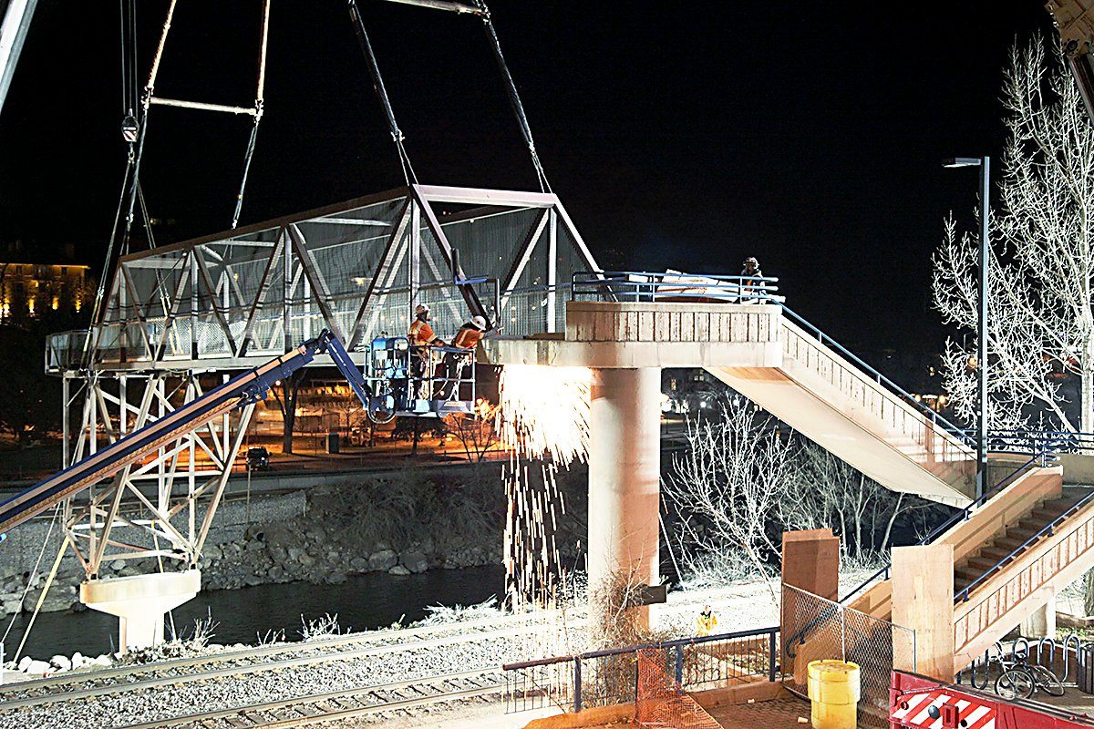 Work began Tuesday night to remove the southernmost sections of the Grand Avenue pedestrian bridge.