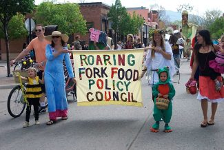 Gwen Garcelon, in blue, holds a banner along with RFFPC co-founder Dawne Vrabel, during a past Potato Day Parade. Stephanie Syson of Colorado Rocky Mountain Permaculture Institute is at right.