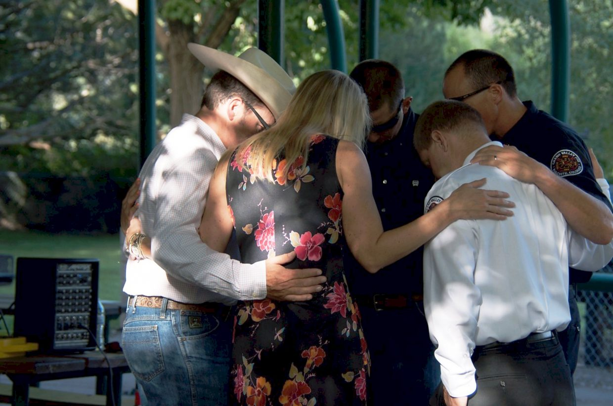 Members of the Grand Valley Fire Protection District say a prayer before the memorial for Sarah Ogden at Cottonwood Park in Parachute last night.