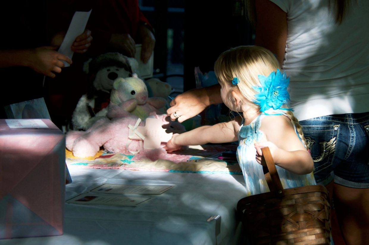 Cathy Redman and daughter Lane place a cross and a stuffed bear on the donation table at the memorial service for Sarah Ogden at Cottonwood Park in Parachute last night.