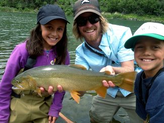 Taylor Creek guide Christian Hill poses with with some excited young clients after this monster trout was landed.