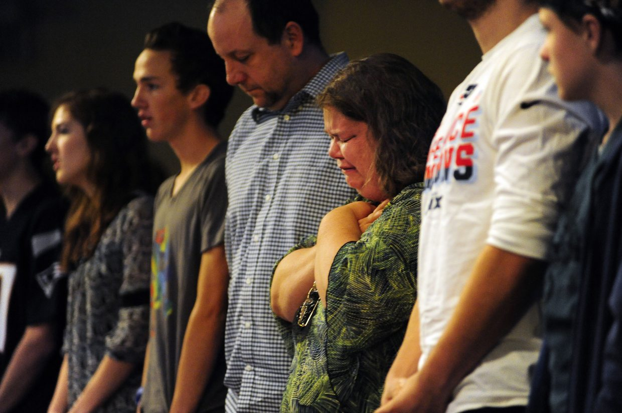 Jennifer Churchill, center, a member of Hope Chapel in Colorado Springs, begins to cry as the congregation sings praise songs on Sunday, during its first service since one of their elders, Garrett Swasey, a 44-year-old police officer at the University of Colorado, was killed during Friday's shooting at a Planned Parenthood clinic in Colorado Springs.