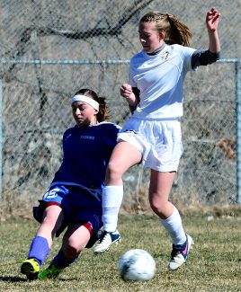 Rifle High School's Katie Harman (right) figuts for possession of the ball with Brittany Young of Coal Ridge during a girls soccer match Saturday morning at Rifle High School. The Titans defeated the bears, 8-0.