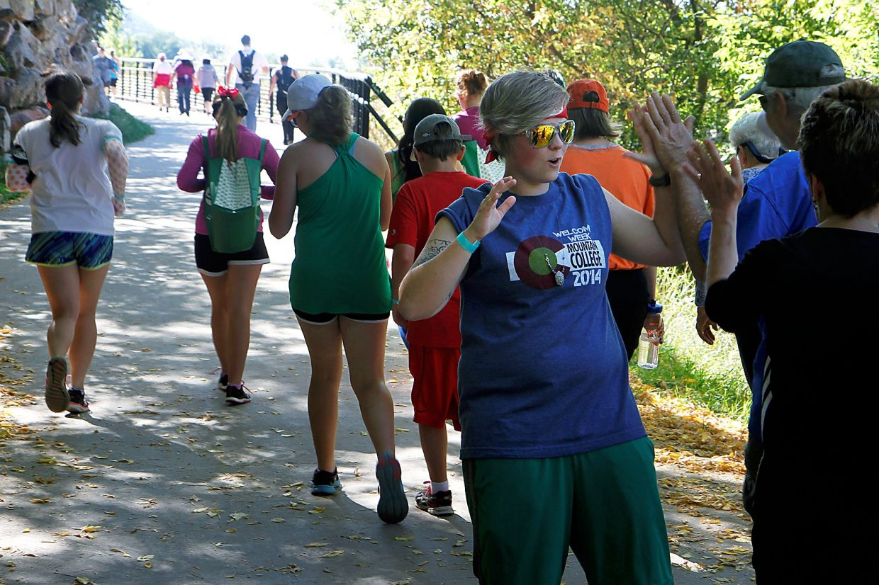 Katy Jones gives out high fives during Rally the Valley's 4-mile walk on the Rio Grande Trail.