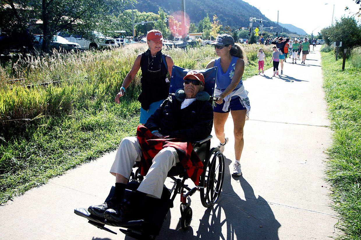 Arlene Ginn and Virginia Reynolds push John Ginn alonge the Rio Grand Trail during Rally the Valley's 4-mile walk.