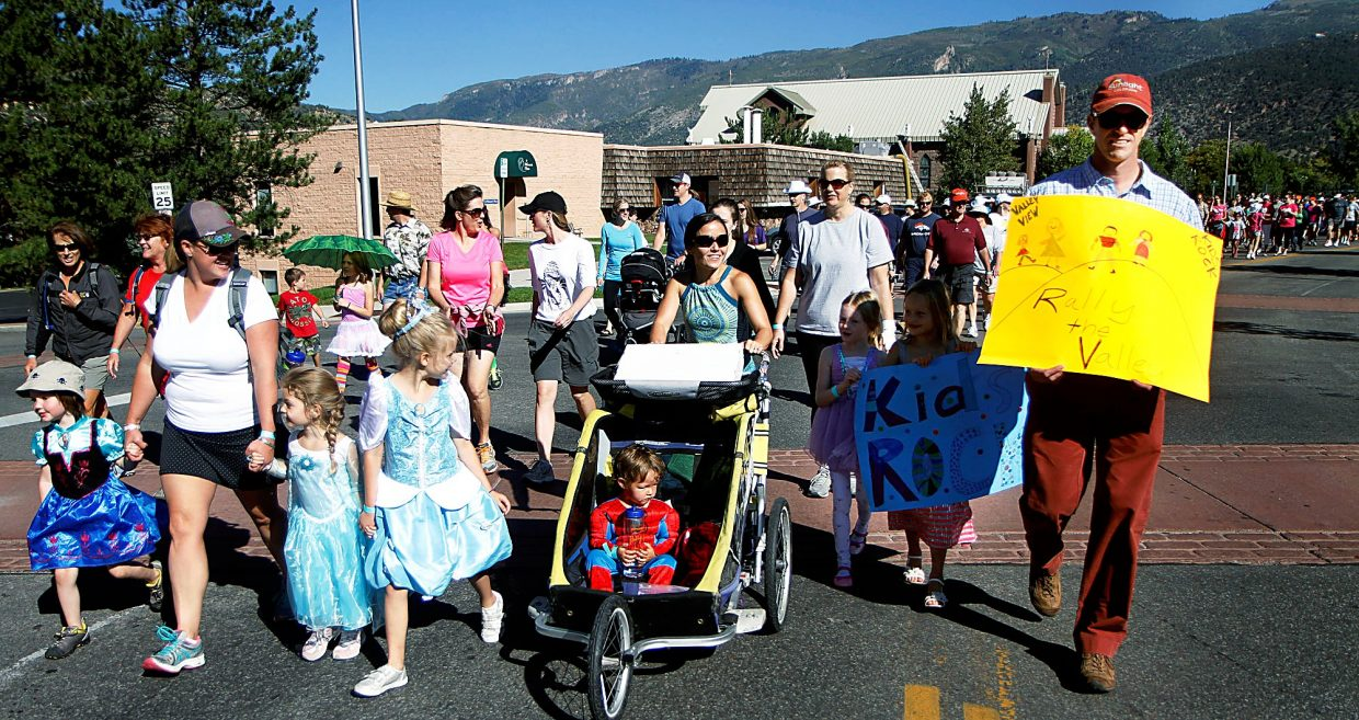 Walkers in Peyton's 1.5-Mile Family Parade walk past Valley View Hospital holding signs and dressed in costume.