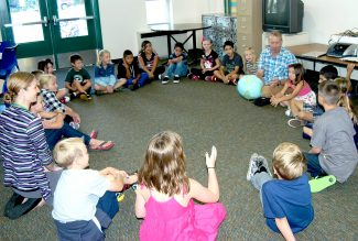 Students in Jim Hardcastle's (plaid shirt at right) third grade class at Sopris Elementary School in Glenwood Springs pass a globe beach ball around the circle to take turns telling a little bit about themselves on Monday, which was the first day of class for most students in Roaring Fork Re-1 schools in Glenwood Springs, Carbondale and Basalt. Incoming Re-1 kindergarten students have until Sept. 3 before they begin school.