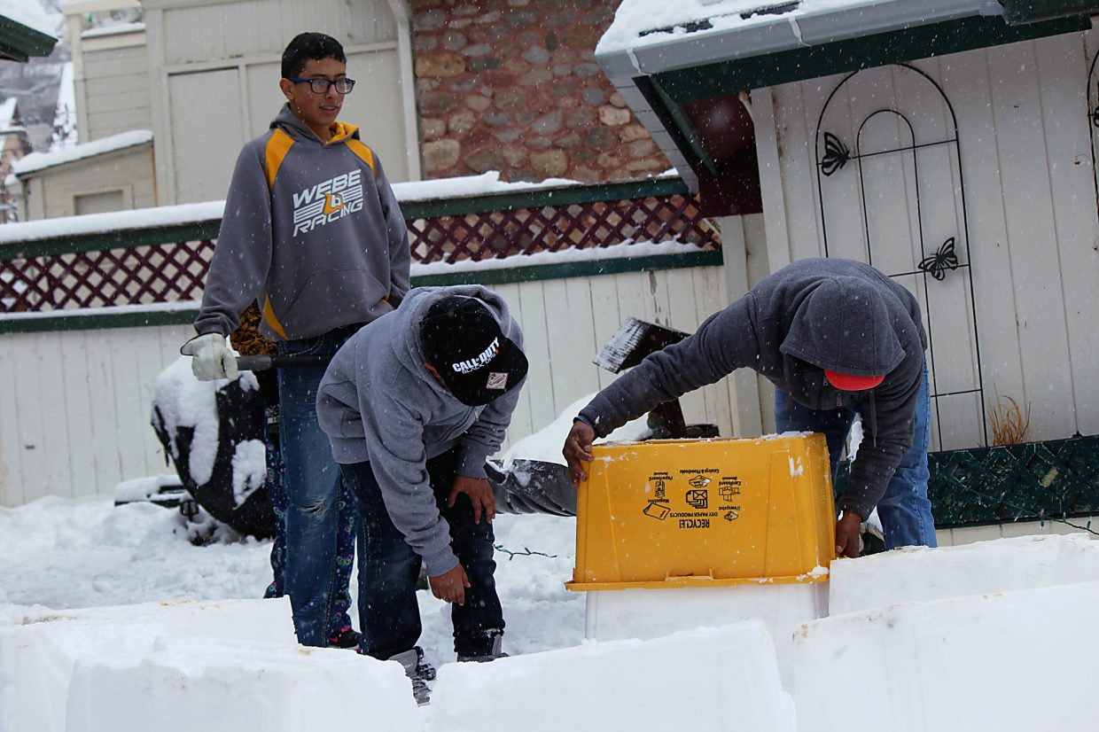 Brothers Abdon, left, and Jovany Rivera help John Mestas, right, make an igloo by packing snow into a recycling bin at the corner of East Avenue and Third Street in Rifle on Monday, Feb. 1.