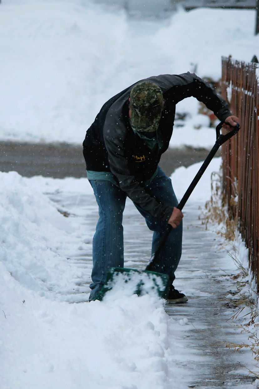 Donnie Cook shovels snow Monday, Feb. 1, at the intersection of Third Street and Whiteriver Avenue in downtown Rifle.