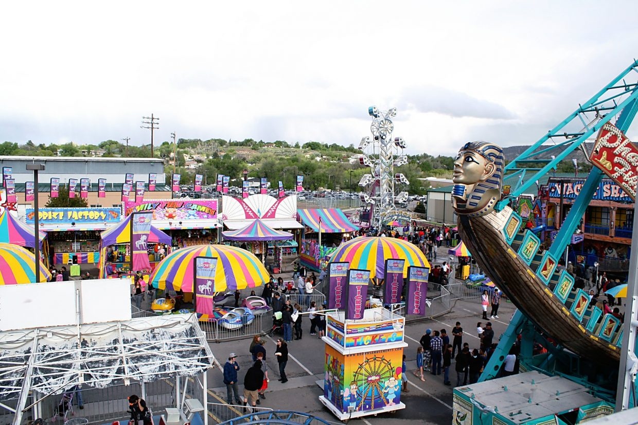 People mingle through the rides at the 19th annual Rifle Rendezvous after a brief shower Saturday afternoon. Despite the rain and cooler temperatures, people showed up all three days to make this year's festival a success, said Scott Brynildson, president of the Rifle Rendezvous.