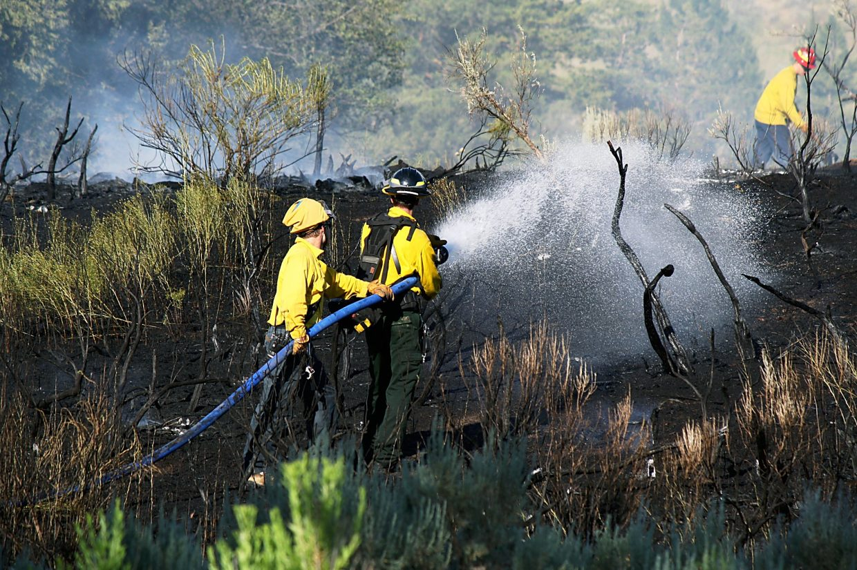 Colorado River Fire Rescue firefighters douse the smoldering ground where a fire burned 2.22 acres east of Whiteriver Avenue behind the Rifle Police Station Sunday evening.