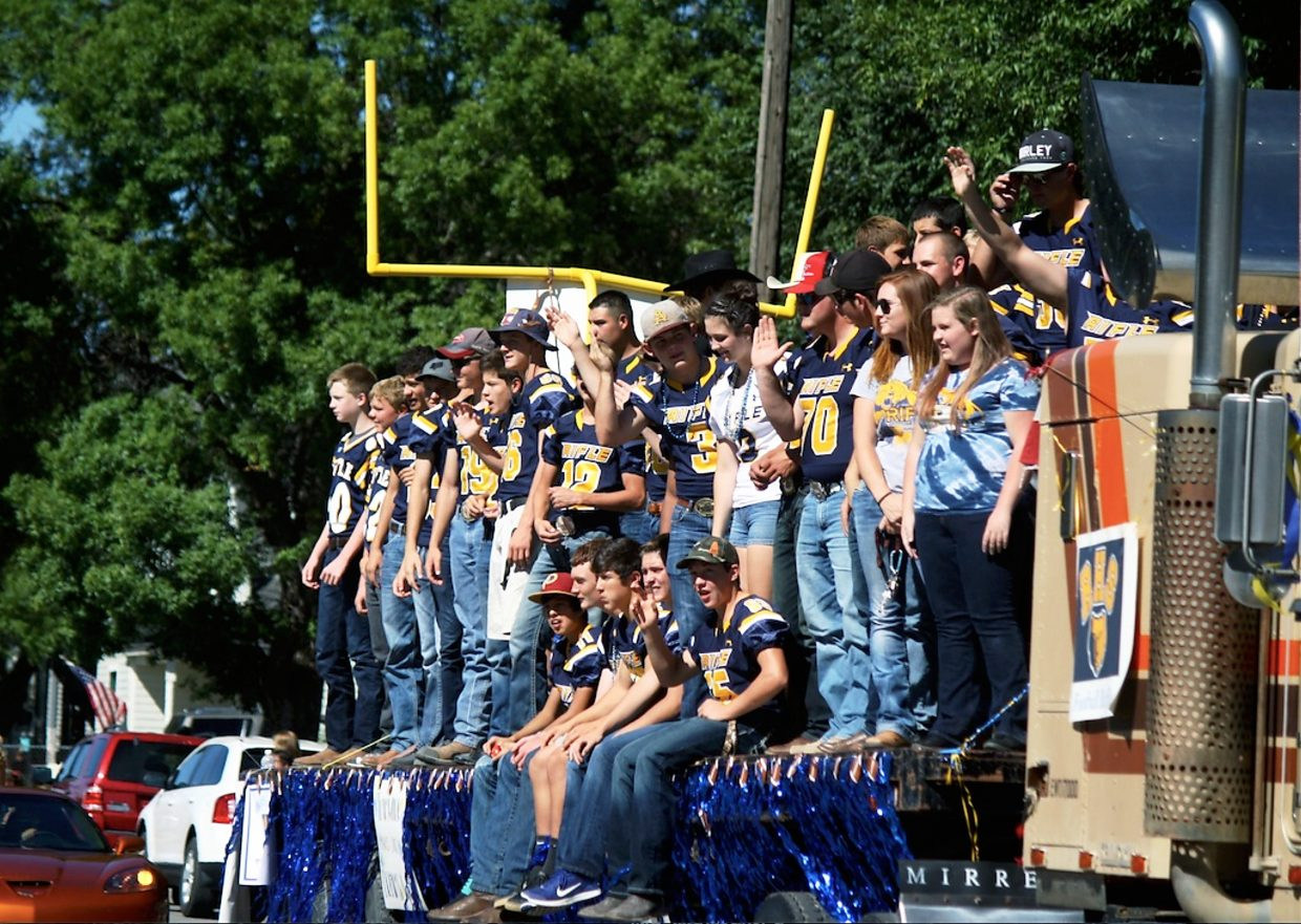 Rifle's football team, with the largest float in the homecoming parade, rolls down Railroad Avenue.
