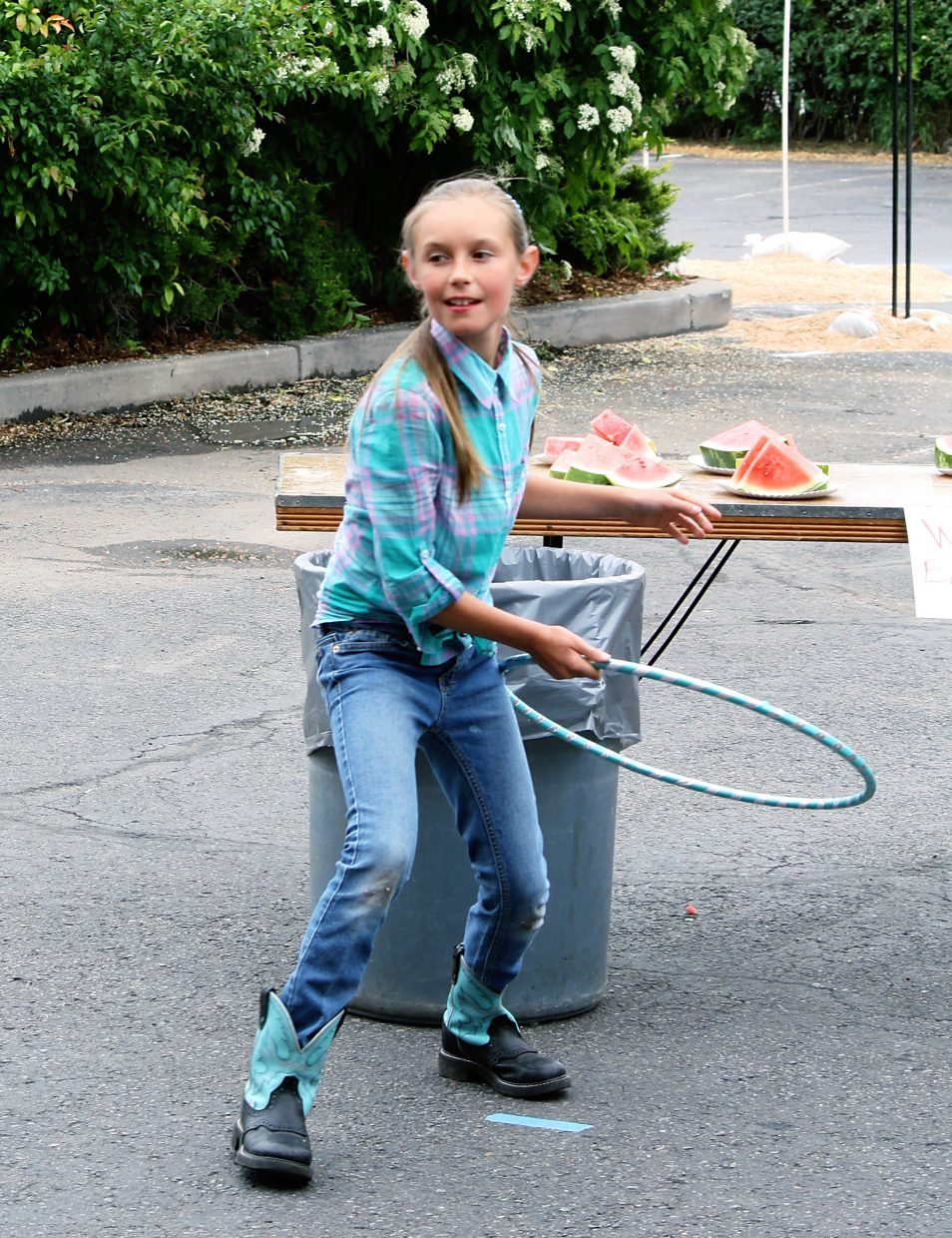 Chloe Simons tosses a hula-hoop Saturday in the ring the milk can challenge at Rifle Heritage Day.