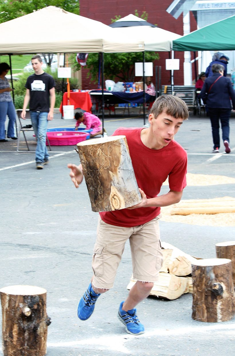 Jamin Wright takes off with his log in a wood splitting competition at Rifle Heritage Day Saturday. Participants were required to pick a log; race down to the chopping block; split the log into four pieces with an ax; before picking up all four pieces and racing back to the finish line. Wright completed the task in 19 seconds.