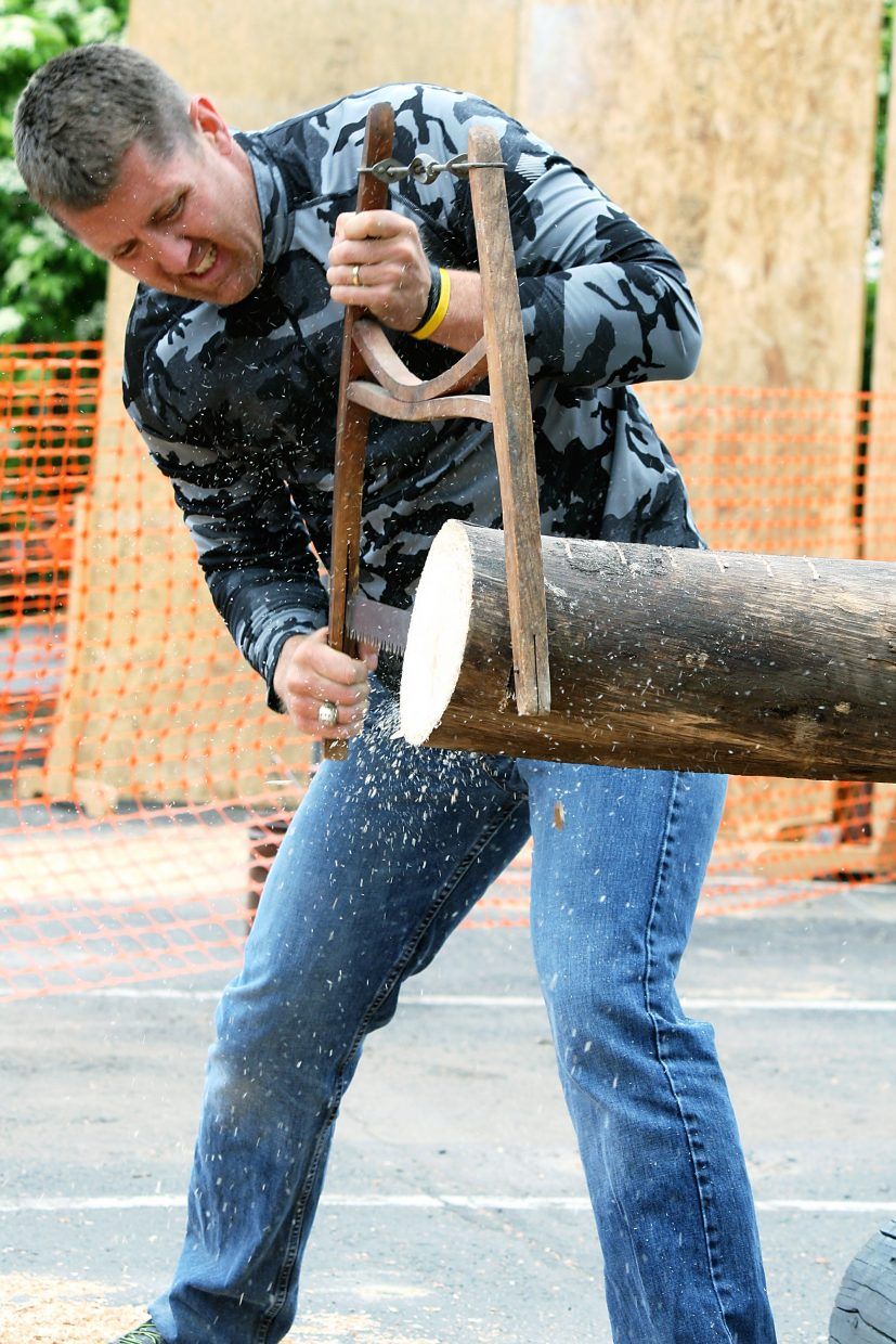 Sawdust flies through the air as Jim Lord nears the end of the bucksaw challenge Saturday.