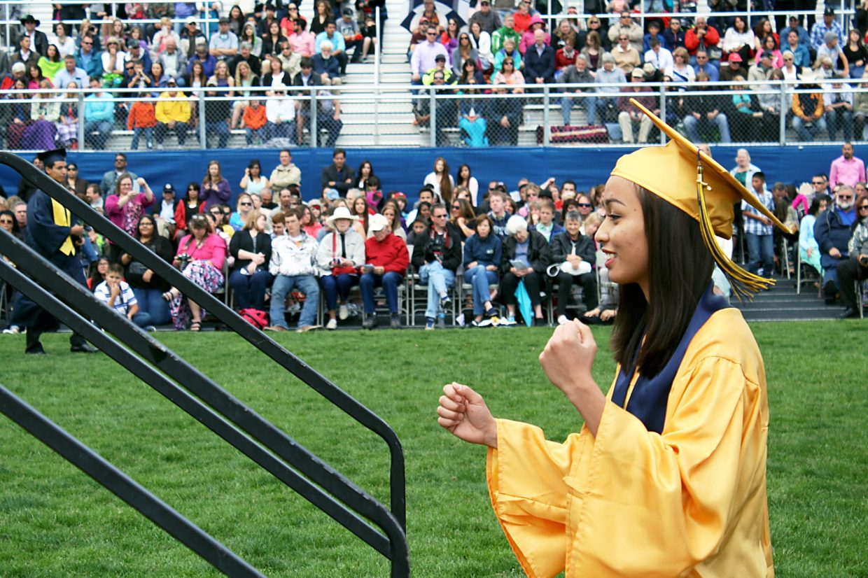 Naphawan Jamjaroenjit pumps her fist before receiving her diploma.