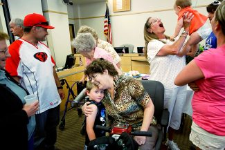 Glenwood Springs City Clerk Robin Unsworth hugs her grandson Eithan Johnson, as she is surrounded Monday by friends and family during her retirement party at City Hall.