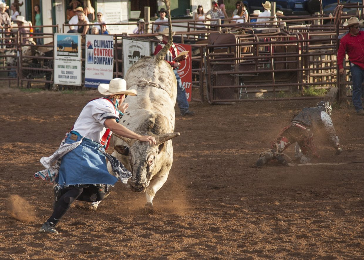 Rodeo clown Beau Werts works to distract the bull from the cowboy as he makes his way to the fence at the Carbondale Wild West Rodeo.