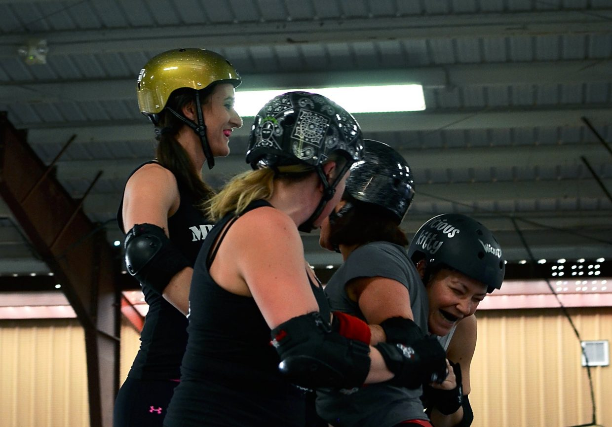 Rachel Marquez and Roslyn Bernstein laugh during roller derby practice.