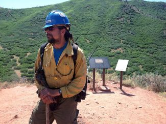 Mike Watson, a current member of the Prineville, Oregon Hot Shots, stands at the overlook on Storm King Mountain Sunday, answering questions and assisting family members making the hike on the 20th anniversary of the fire there that killed 14 wildland firefighters. Nine of the 14 were members of the Prineville crew.