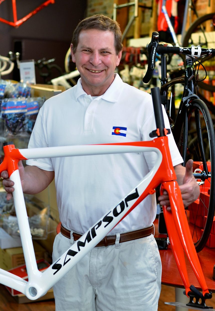 Eric Sampson shows off one of his bikes at his new showroom in downtown Glenwood Springs.