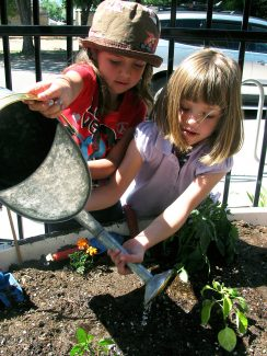 """Kaysha Fuller, left, and Bailey Coy, both 5 and from Joyful Joyce's Daycare in Silt, helped plant a vegetable garden on the patio of the Silt Library on Wednesday during story hour. The garden is a collaboration between Fat City Farmers and the Silt Library, which recently received a $2,000 mini-grant from LiveWell Garfield County. """"We're planting eight garden beds and combining stories with healthy snacks and taking care of the gardens so the children can experience the joys of fresh, healthy food and great literature together,"""" said Illene Pevec, program director for Fat City Farmers. The garden beds were donated by The Kitchen Community, a national foundation, and the plants were grown and donated by Yampah Mountain High students working with Growing Food Forward and Roaring Fork High students."""