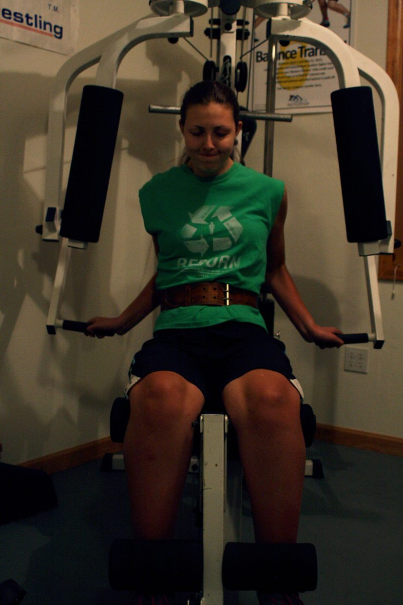 Quincey Snyder takes a deep breath before kicking her legs up on the leg-extension machine. Snyder wakes up early every morning to work out with her father in their home gym.
