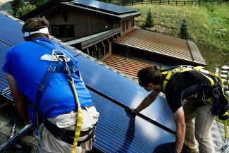 New solar panels are placed into position by Active Energies insallers Chris Caruso, right, and Matt Stephens, on another home in Edwards Point which sees plenty sunlight Wednesday in Edwards.