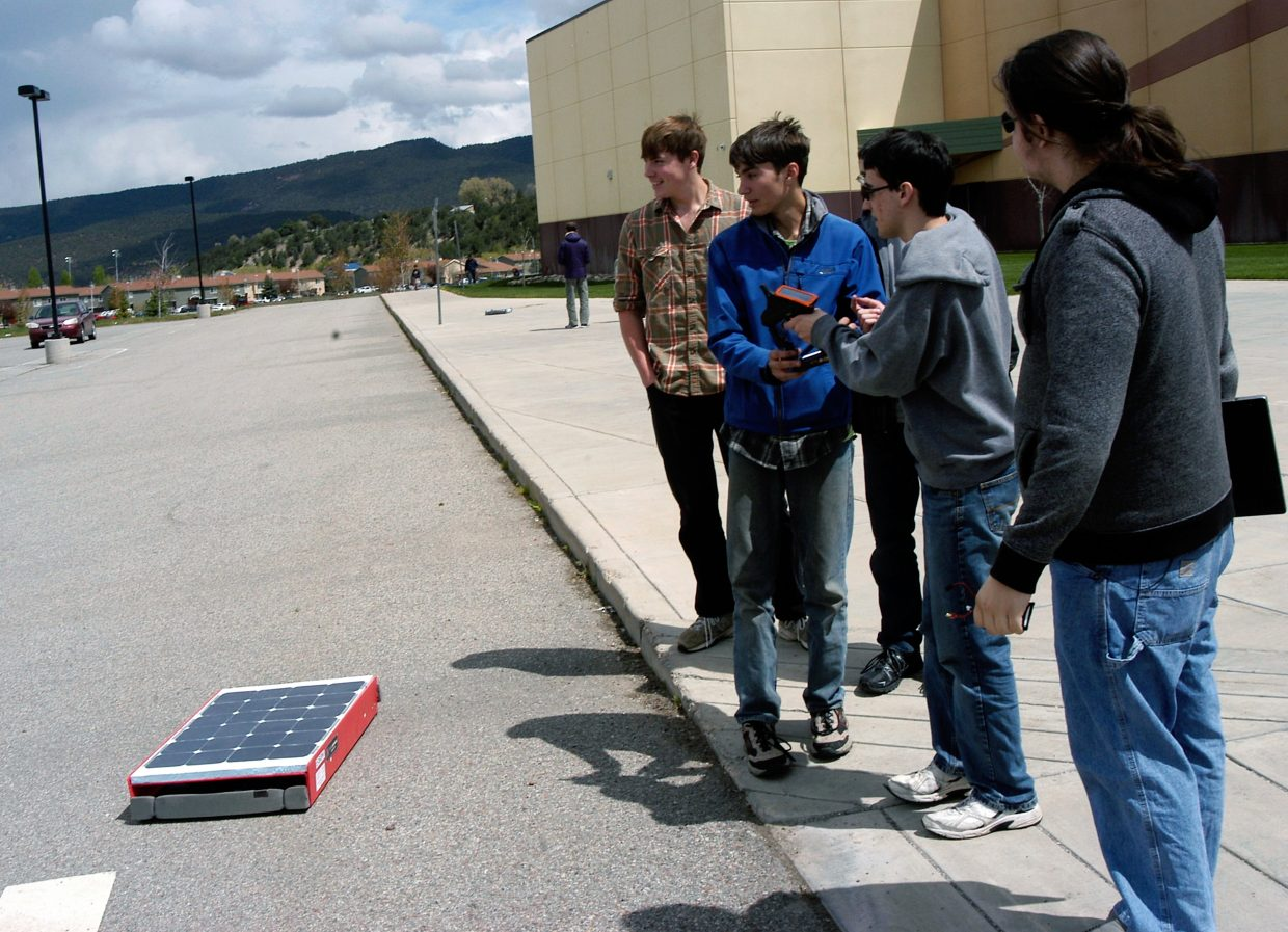 Yampah High School graduate Jacob Sarver, right, looks on as Glenwood Springs High School Solar Rollers team members, from left, Forest Rappe, Anthony Parker and Ryan Scott, get ready to run their remote-controlled solar car during speed trials at the Energetics Education Solar Rollers competition Saturday at Roaring Fork High School in Carbondale. Teams from several area high school participated in speed and head-to-head racing events.