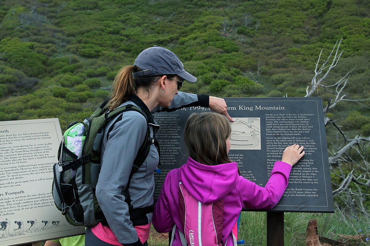 Amanda Maurer, left, and her daughter Ashley read about the fire on Storm King Mountain.