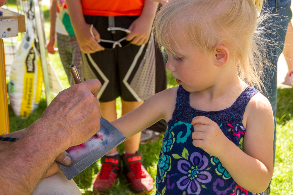 Two year old Mavis Kanble getting a cat tattoo at the Strawberry Days Festival at Sayre Park.