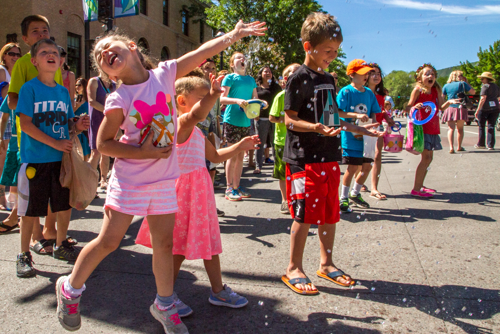 Kids enjoy being sprayed with water during a hot morning at in downtown Glenwood Springs for the 119th Annual Strawberry Days Parade.