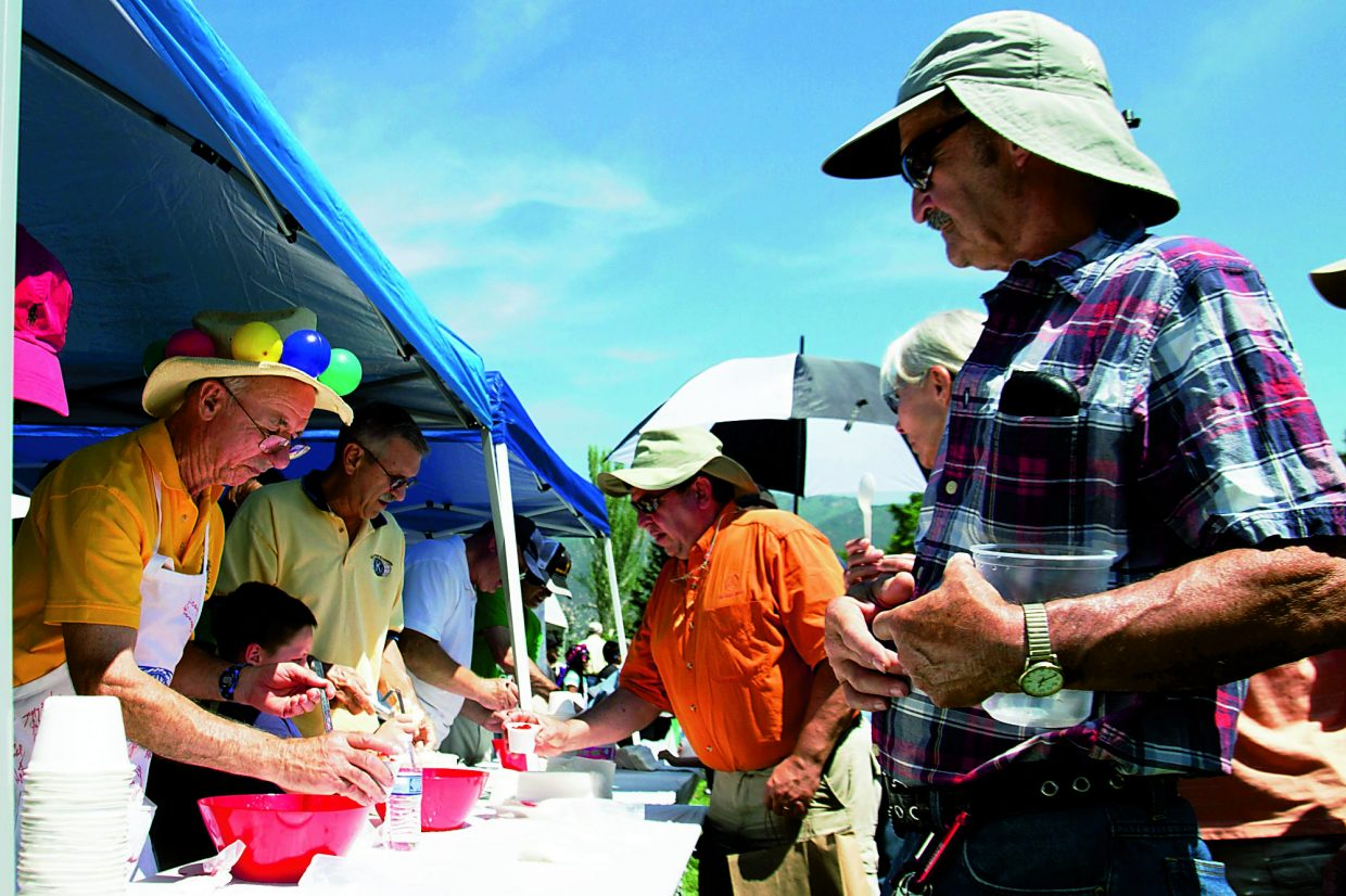 People wait in line to recieve their free ice cream and strawberry topping at Sayre Park during Strawberry Days 2015.