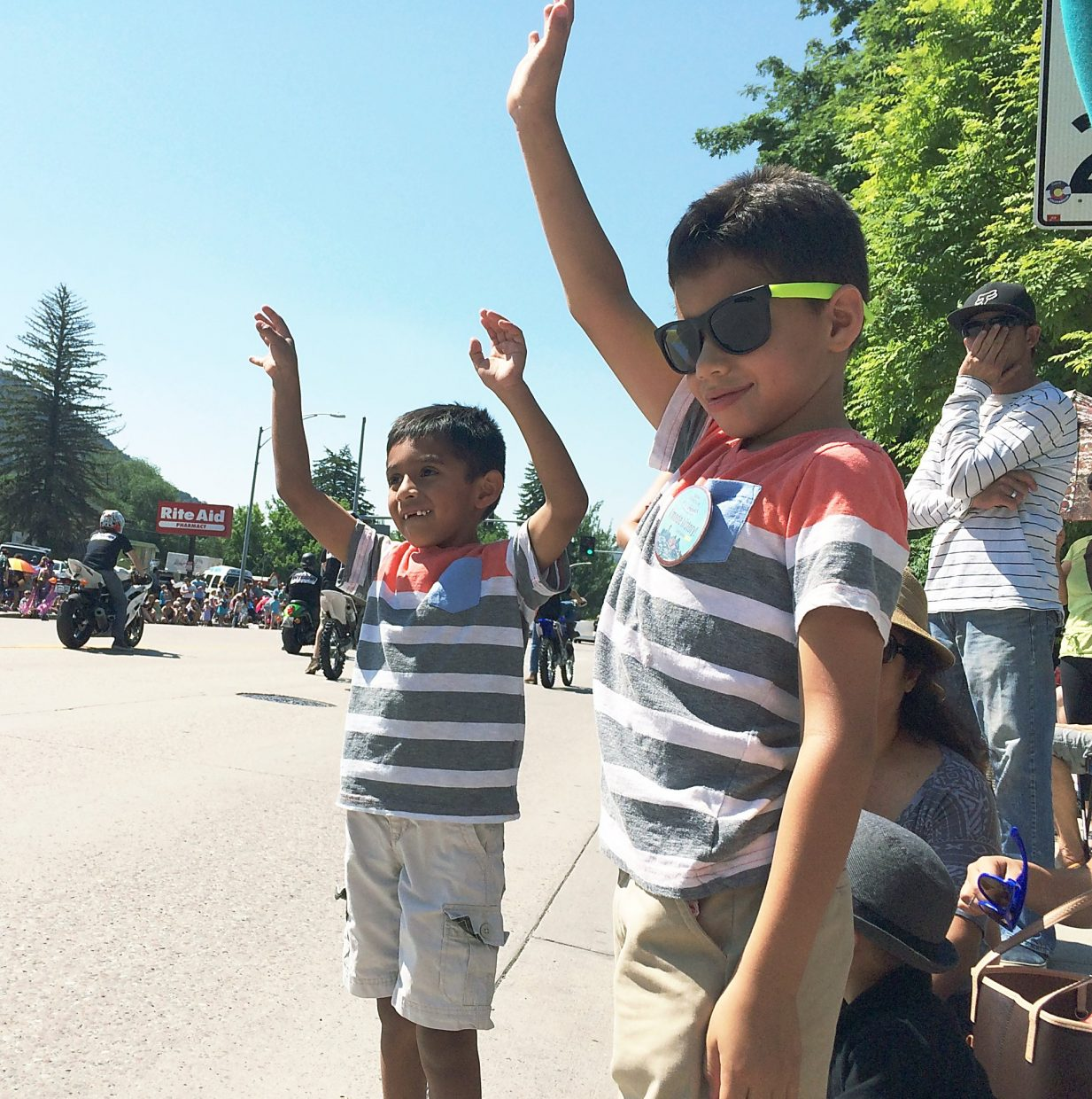 The Fuentes brothers, Ian in the yellow-framed glasses and Hillel in the blue frames, wave to try to get the attention of parade participants throwing candy at the 2015 Strawberry Days parade.