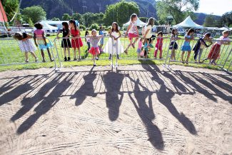 Christopher Mullen Post Independent Strawberry Princesses wait along a fence after practicing crossing the catwalk during the Princess Party, at Sayre Park June 19.