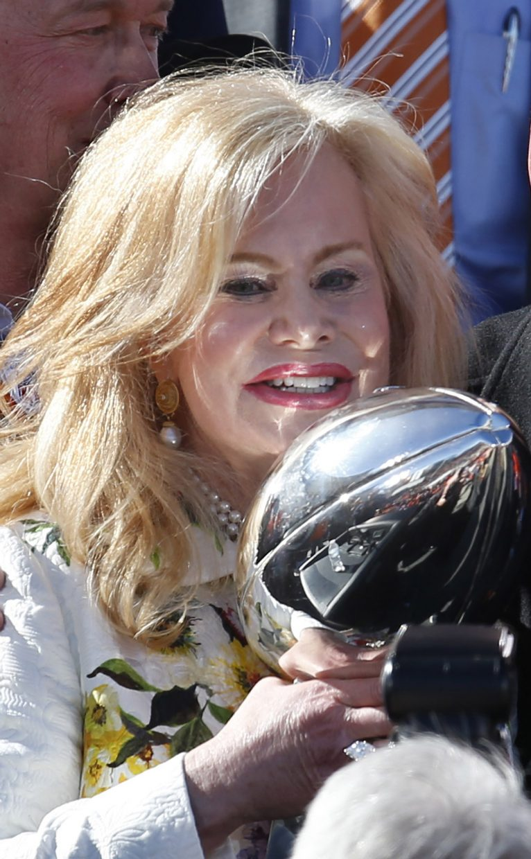 Annabelle Bowlen, wife of Denver Broncos owner Pat Bowlen, is reflected by light shining off the Lombardi Trophy at a rally following a parade through downtown Tuesday, Feb. 9, 2016 in Denver. Fans crowded into Denver's downtown to salute the Broncos for the team's victory over the Carolina Panthers in Super Bowl 50. (AP Photo/David Zalubowski)