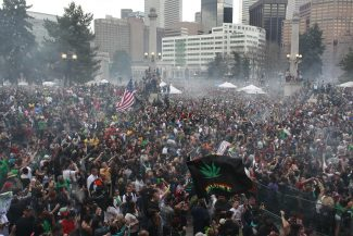 FILE - In this April 20, 2013 file photo, members of a crowd numbering tens of thousands smoke marijuana at the Denver 4/20 pro-marijuana rally at Civic Center Park in Denver. With Denver poised to allow recreational marijuana sales, Mayor Michael Hancock wants to act now to stop public pot smoking. Under a city ordinance to be introduced Monday, Oct. 14, 2013, possessing or smoking marijuana would be illegal in city parks and other specified areas, and the smell of marijuana coming from private property would be barred. (AP Photo/Brennan Linsley, File)