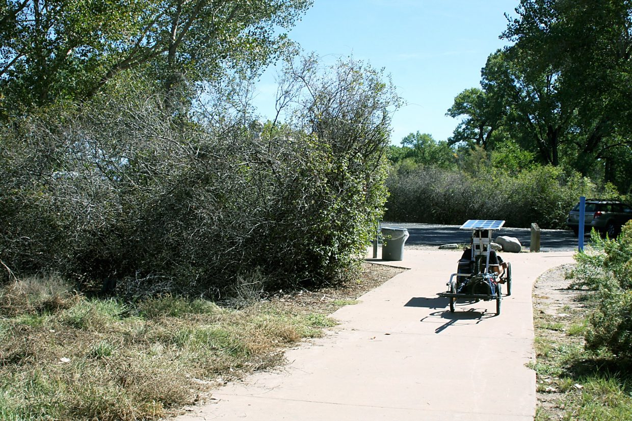 Eric Goakes, a Grand Junction resident, rides away with his bike-boat after a visit to Connected Lakes.