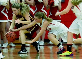 Madison Murphy of Golden (left) battles for possession of the ball with Jamie Crowley of Glenwood Springs during the first half of Friday night's Class 4A state tournament game at Glenwood Springs High School. Glenwood won the game, 48-44.
