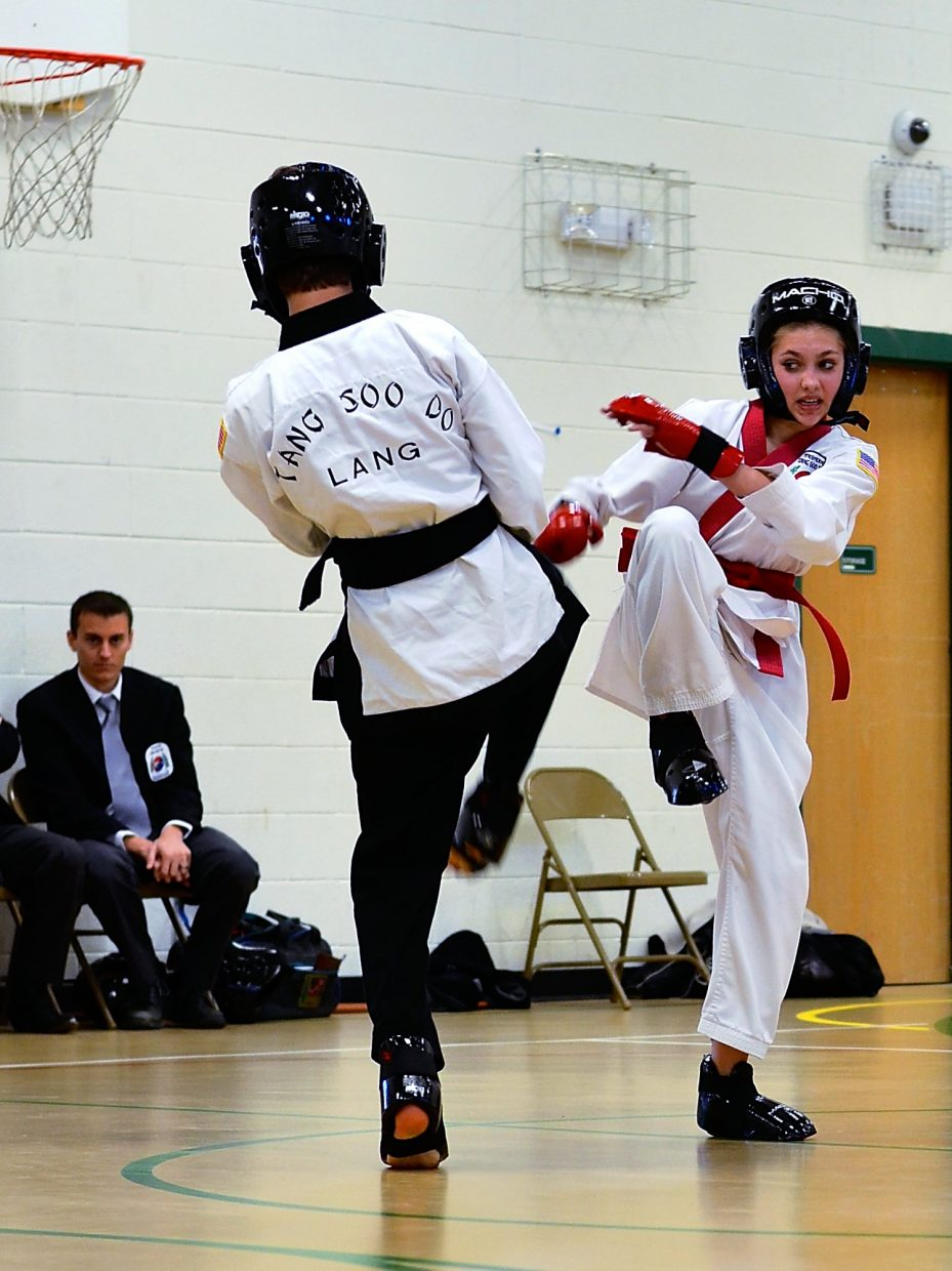 Thirteen year old Kayle Justice (red belt) spars with a partner during her black belt test on Saturday morning at Sopris Elementary School.
