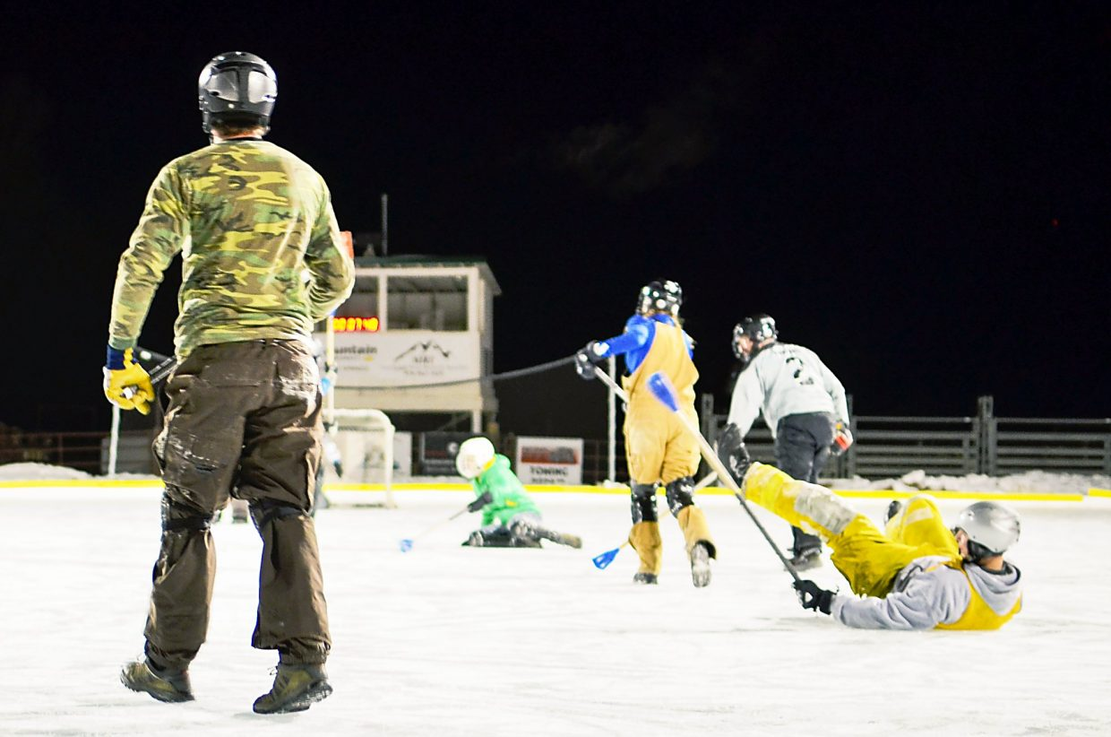 Broomball players struggle to right themselves on the ice after a play.