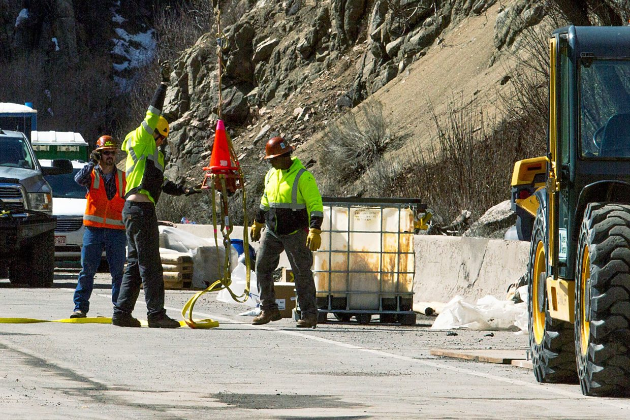 Crews on the ground hooked up cables and a tank to the helicopter as part of the rockfall netting operations.