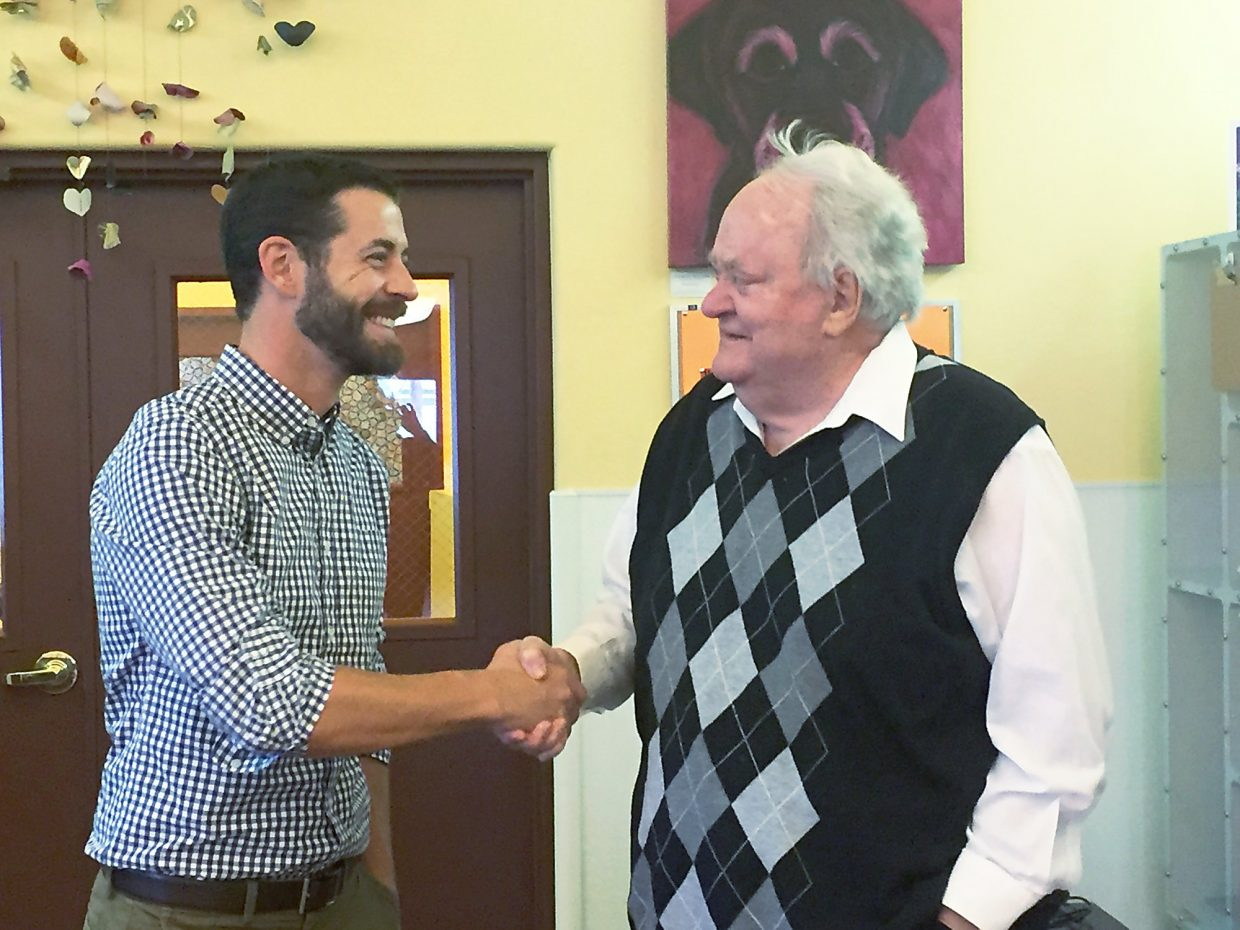 Wes Boyd is congratulated by Jim Calaway for becoming the new executive director of C.A.R.E. on Nov. 16th.