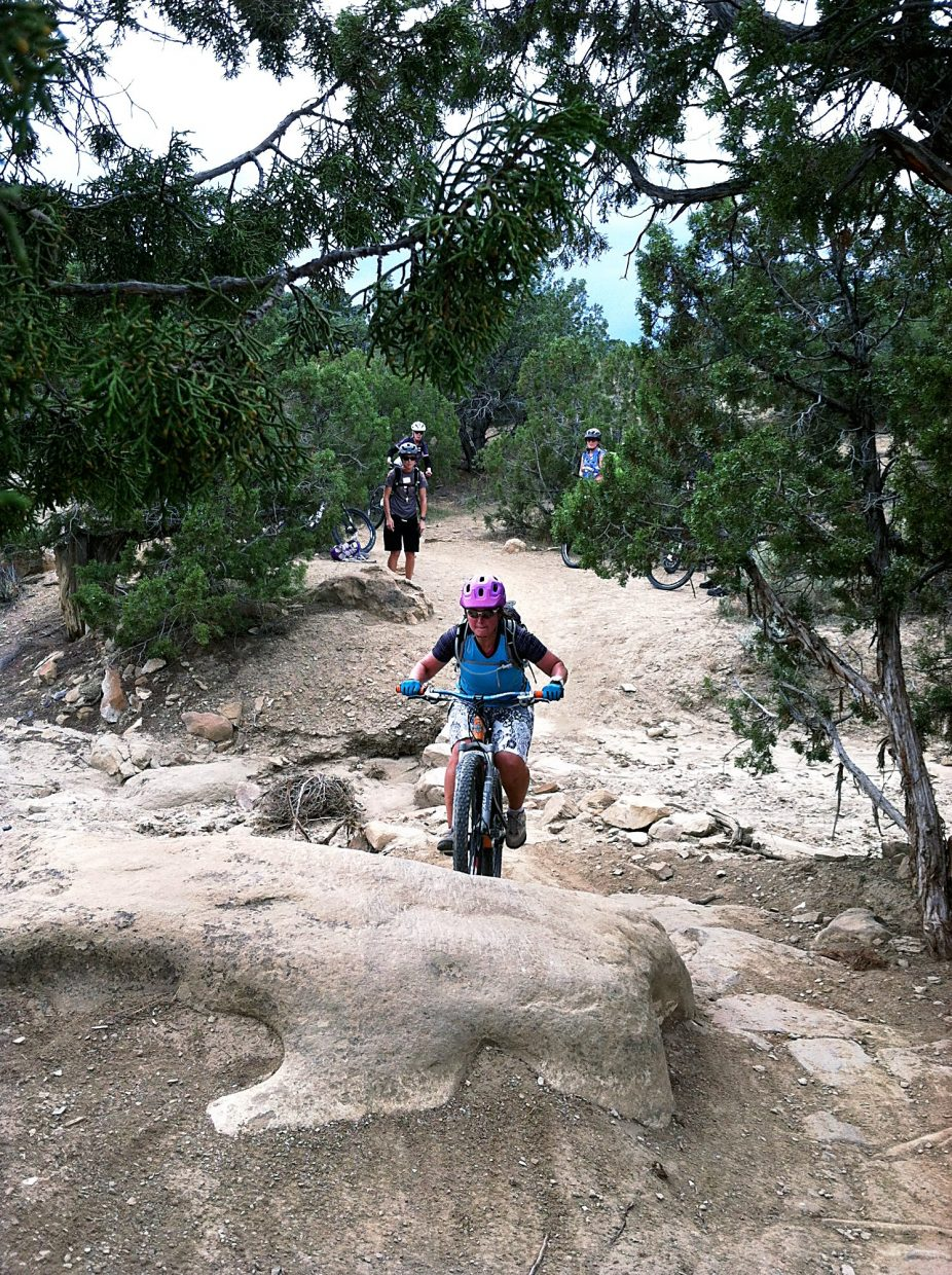 One of the riders attending the Dirt Series Skills Camp in Fruita attempts to ride up a slab rock using skills learned at the camp, which include keeping low on the bike, using the right gear, and looking ahead.